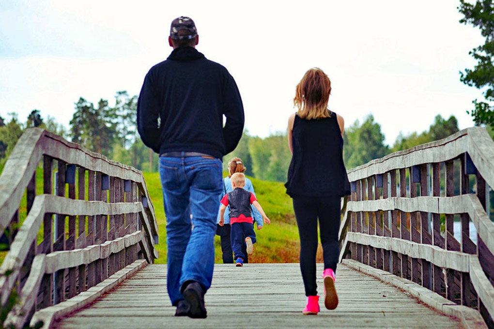 Family with young children walking on bridge.