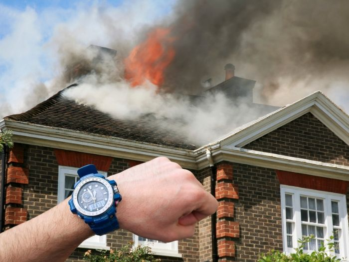 Arm with watch in front of a house on fire.