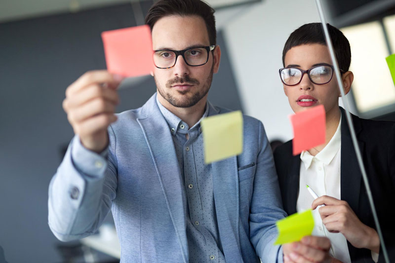 2 people in a business meeting looking at post-it notes.
