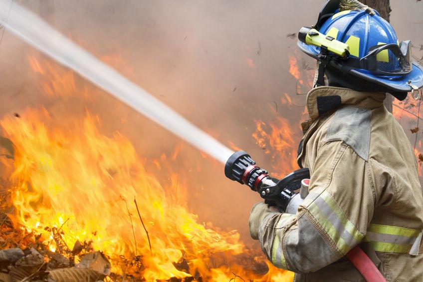 Fireman battling a fire with water hose.