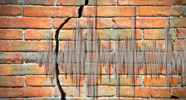 Graph of earthquake activity overlaid on wall showing crack.
